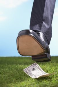 Businessman stepping on fifty-dollar bill in grass close-up of f